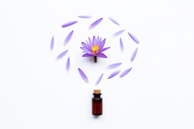 Aceite esencial con la flor de loto púrpura en blanco.