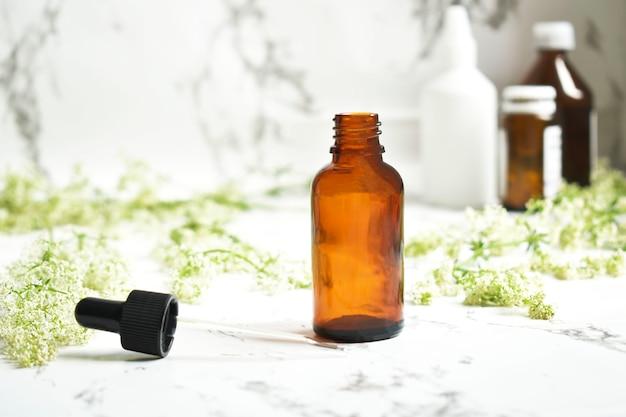 Aceite esencial en frasco de vidrio ámbar, con gotero de vidrio y flores de tomillo sobre una mesa de mármol.