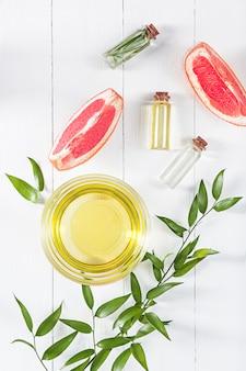 Aceite esencial en frasco de vidrio con pomelo fresco y jugoso y tratamiento de belleza con hojas verdes.
