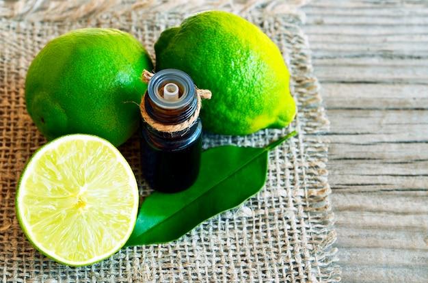 Aceite esencial de lima en una botella de vidrio con frutas frescas de lima para spa, aromaterapia y cuidado corporal.