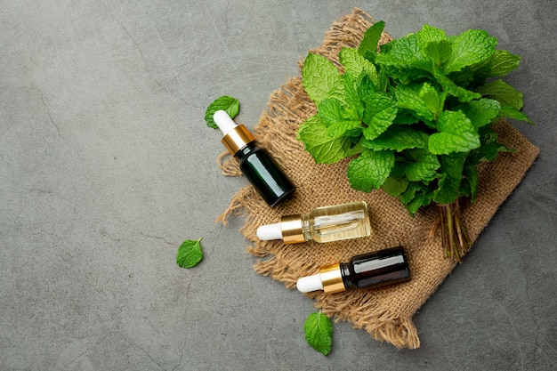 Aceite esencial de menta en botella con menta verde fresca