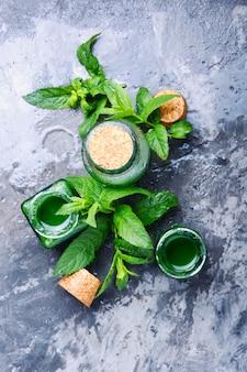 Aceite esencial de menta con hojas verdes.