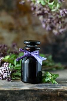 Aceite esencial de orégano en botella de vidrio sobre fondo de madera. copia espacio