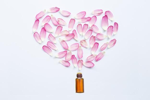 Aceite esencial con pétalos de loto rosa sobre blanco.