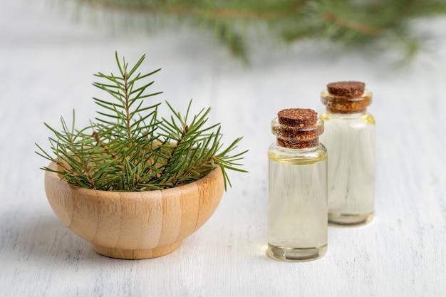 Aceite esencial de pino en una botella de vidrio. enfoque suave. fondo de madera blanca.