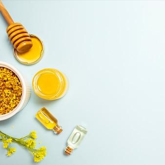 Aceite esencial; polen de abeja y miel con flor fresca amarilla sobre fondo azul