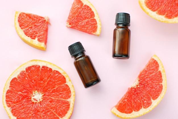 Aceite esencial de pomelo en frascos oscuros, rodajas de pomelo maduro en plano rosa.