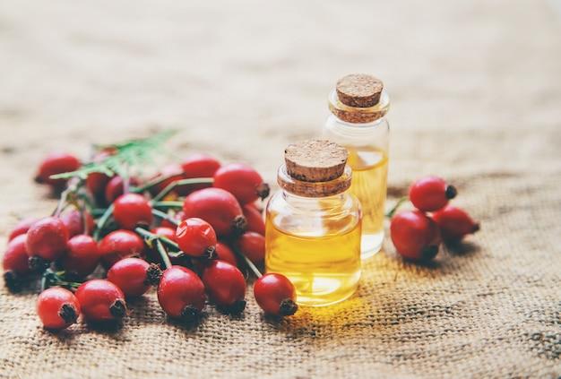 Aceite esencial de semilla de rosa mosqueta en una botella pequeña. enfoque selectivo.