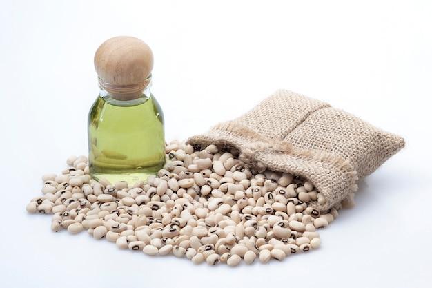 El aceite se extrae de los frijoles blancos y las semillas de frijoles blancos que tienen sacos en una pared blanca.
