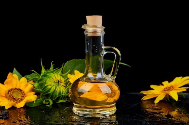 Aceite de girasol en frasco de vidrio, semillas y flores.