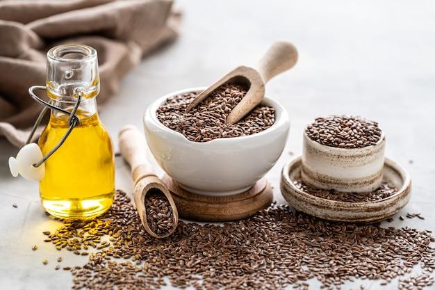 Aceite de linaza en una botella y tazón de cerámica con semillas de lino marrón y cuchara de madera sobre un fondo blanco.