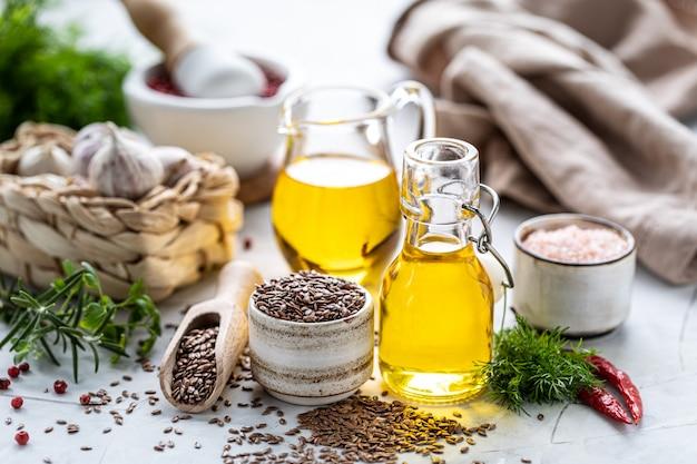 Aceite de linaza en una botella y tazón de cerámica con semillas de lino marrón y cuchara de madera.