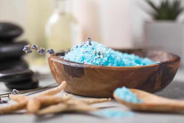 Aceite de masaje botella de aroma esencial y fragancia natural de sal con piedras, velas sobre mesa de hormigón gris.