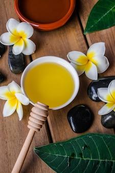 Aceite de masaje, con cuchara de madera de miel, flores y hojas de plumeria,
