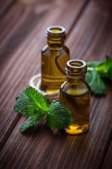 Aceite de menta en botellas pequeñas y menta fresca.