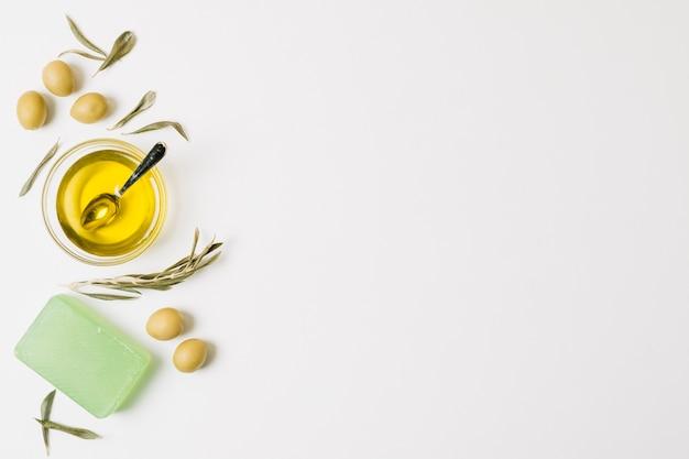 Aceite de oliva con aceitunas y barra de jabón.