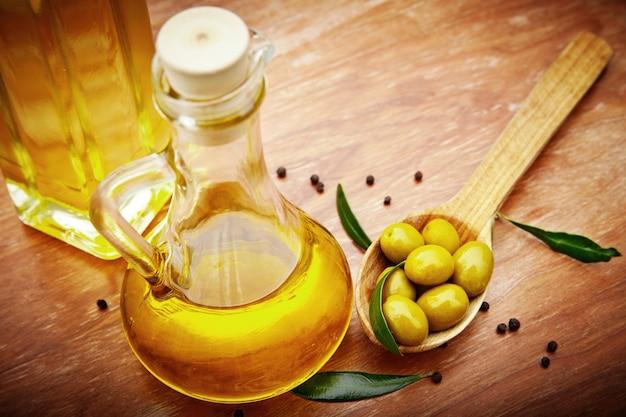 Aceite de oliva con aceitunas frescas sobre madera rústica