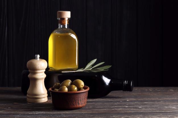 Aceite de oliva, aceitunas verdes y especias en una mesa de madera con espacio para texto.