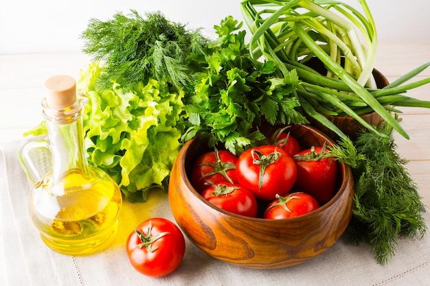 Aceite de oliva, ajo y tomate en un tazón de madera.