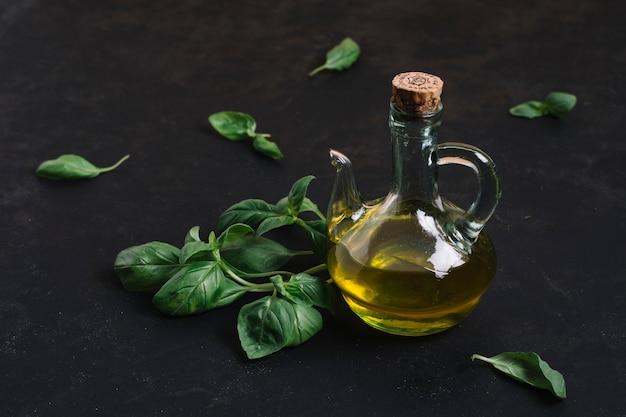 Aceite de oliva embotellado con espinacas a su alrededor.
