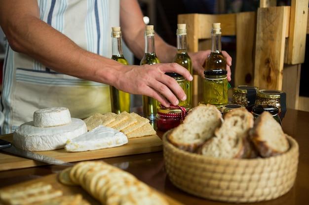 Aceite de oliva, mermelada, pepinillos colocados juntos sobre la mesa