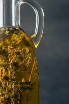 Aceite de oliva natural amarillo transparente con especias dentro en botella de vidrio de cerca.