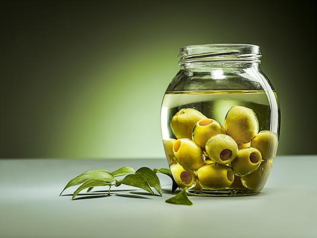 Aceite de oliva y rama de olivo en la mesa de madera