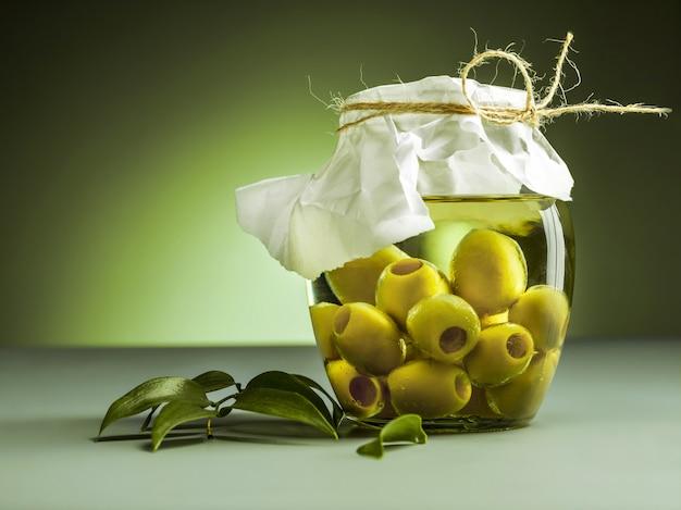 Aceite de oliva y rama de olivo en mesa de madera