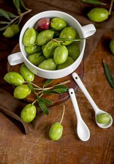 Aceite de oliva y rama de olivo sobre fondo negro.