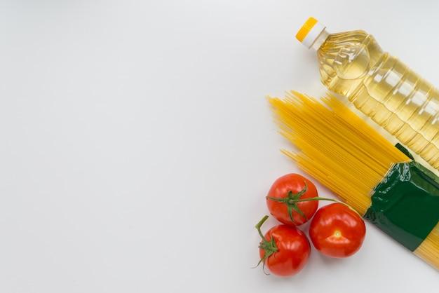 Aceite, pasta y tomates en la superficie blanca.