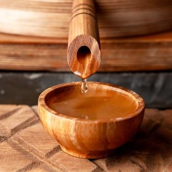 Aceite que fluye en un tazón de madera