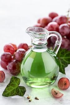 Aceite de semilla de uva en una botella de vidrio con un racimo de uvas.