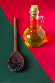 Aceite de semillas de sandía fresca en un frasco de vidrio pequeño y semillas crudas en una cuchara de madera sobre fondo rojo y verde. minimalismo gastronómico