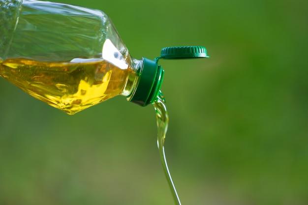Aceite vegetal que vierte de la botella con el fondo de la naturaleza