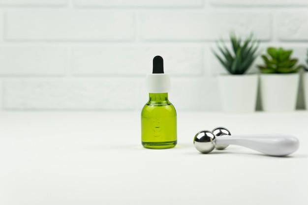 Un aceite verde de cbd y un rodillo facial se colocan sobre una mesa blanca