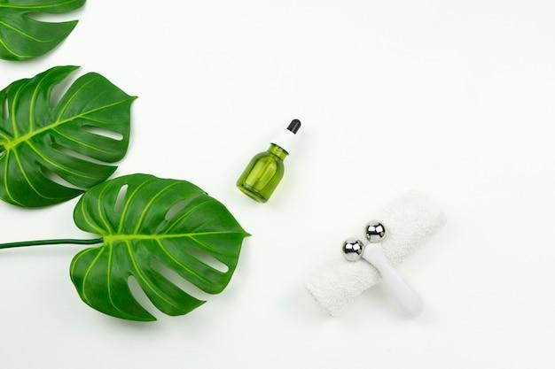 Un aceite verde de cbd, un rodillo facial, una toalla de algodón blanca y hojas verdes de monstera yacen sobre una mesa blanca