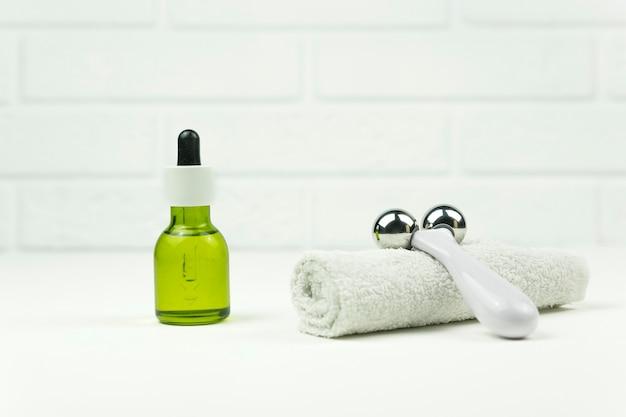 Un aceite verde de cbd, un rodillo para masaje facial y una toalla de algodón blanca se colocan en una bandeja de madera en un baño.