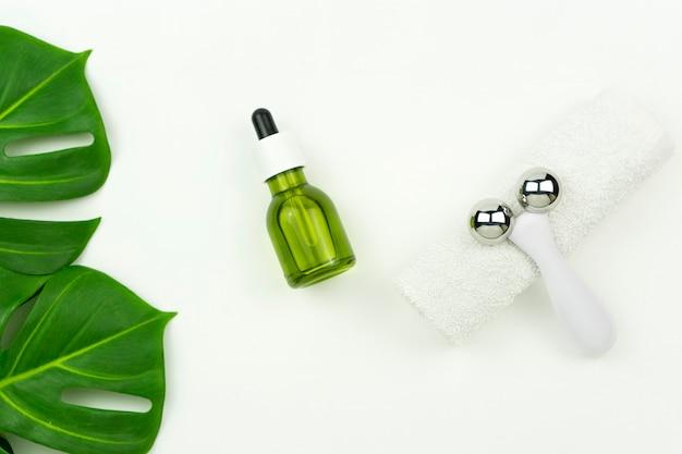 Un aceite verde de cbd, un rodillo para masaje facial, una toalla de algodón blanco y hojas verdes de monstera se colocan sobre una mesa blanca en un baño.