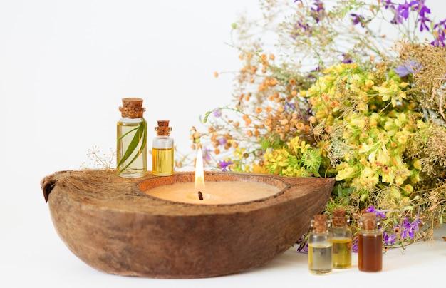 Aceites aromáticos esenciales orgánicos en botellas de vidrio, hierbas medicinales y vela ecológica. enfoque selectivo
