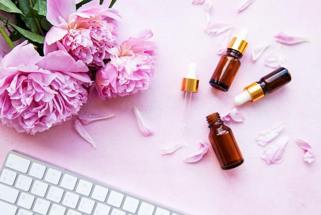 Aceites esenciales de aromaterapia y peonías rosas.