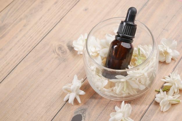 Aceites esenciales de eucalipto en una botella de vidrio y flor sobre fondo de madera
