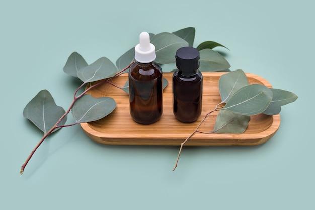 Aceites esenciales con hojas de eucalipto natural sobre fondo pastel de menta, productos de belleza, cuidado de la piel facial, concepto de tratamiento de belleza spa