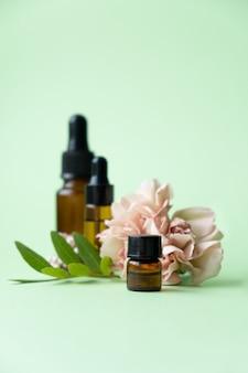 Aceites esenciales, varias botellas con flor de clavel y hojas verdes sobre un fondo verde. concepto de aromaterapia y perfumes.