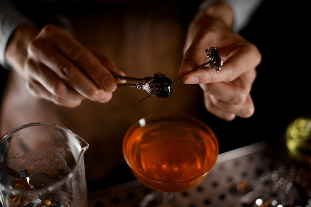 Una aceituna en brocheta en manos de barman