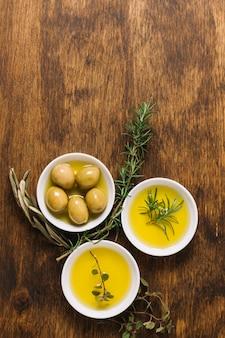 Aceitunas con aceite de oliva y cuencos de romero y espacio de copia