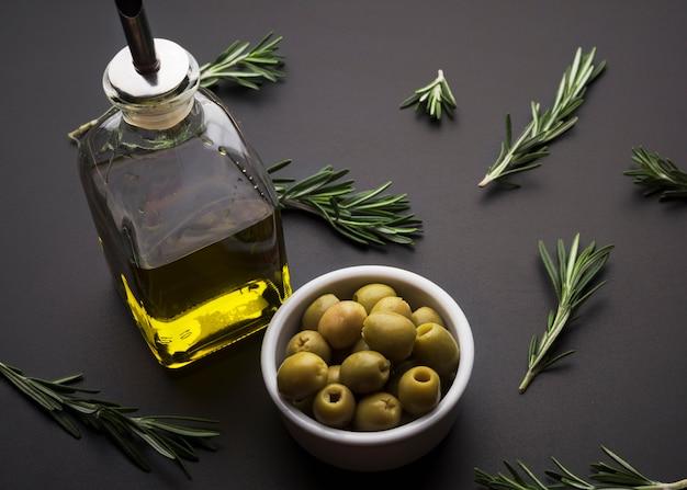 Aceitunas y aceite de oliva y romero sobre superficie de pizarra negra.