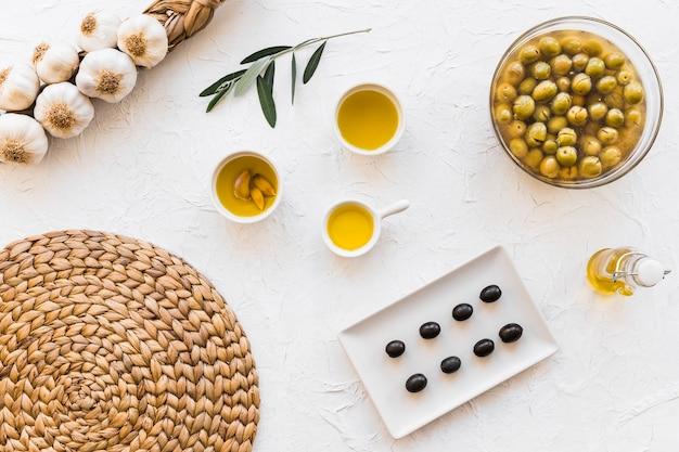 Aceitunas y aceites con racimo de bulbos de ajo y posavasos sobre fondo blanco