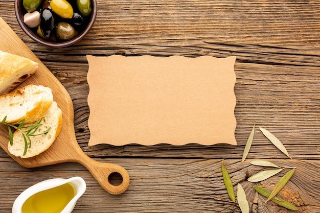 Las aceitunas de alto ángulo mezclan el platillo de pan y aceite con una maqueta de cartón