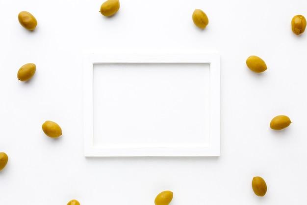 Aceitunas amarillas con maqueta de marco blanco