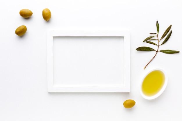 Aceitunas amarillas y platillo de aceite con maqueta de marco